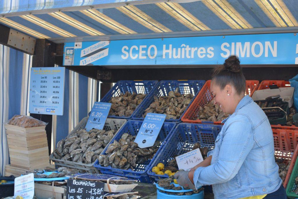 Femme souriante à son stand d'huîtres au marché qui ouvre une huître