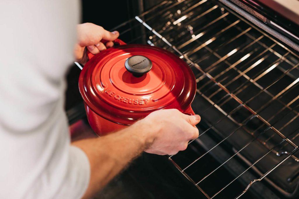Mains d'un cuisinier qui sortent une cocotte rouge du four