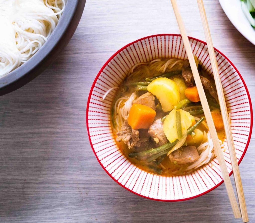 Bol rouge contenant un bouillon de curry rouge avec des légumes, des nouilles et de la viande.