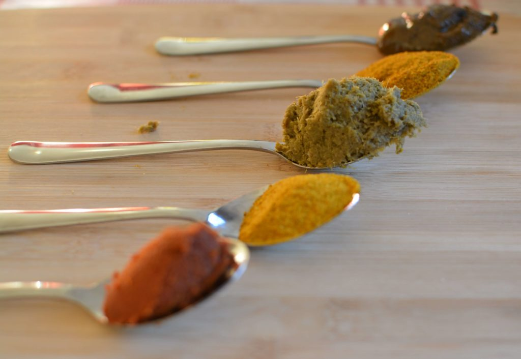 5 cuillères alignées contenant du curry rouge, jaune, vert, en pâte et en poudre