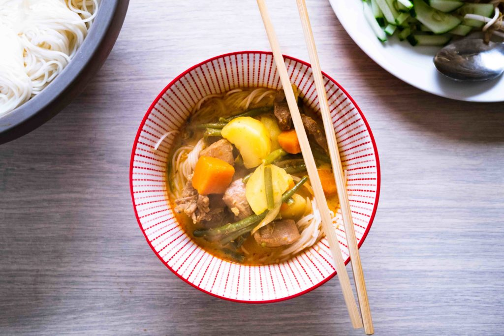 Bol rouge contenant un bouillon de curry rouge avec des morceaux de pommes de terre, des carottes, des nouilles blanches, de la viande et une paire de baguettes posées dessus