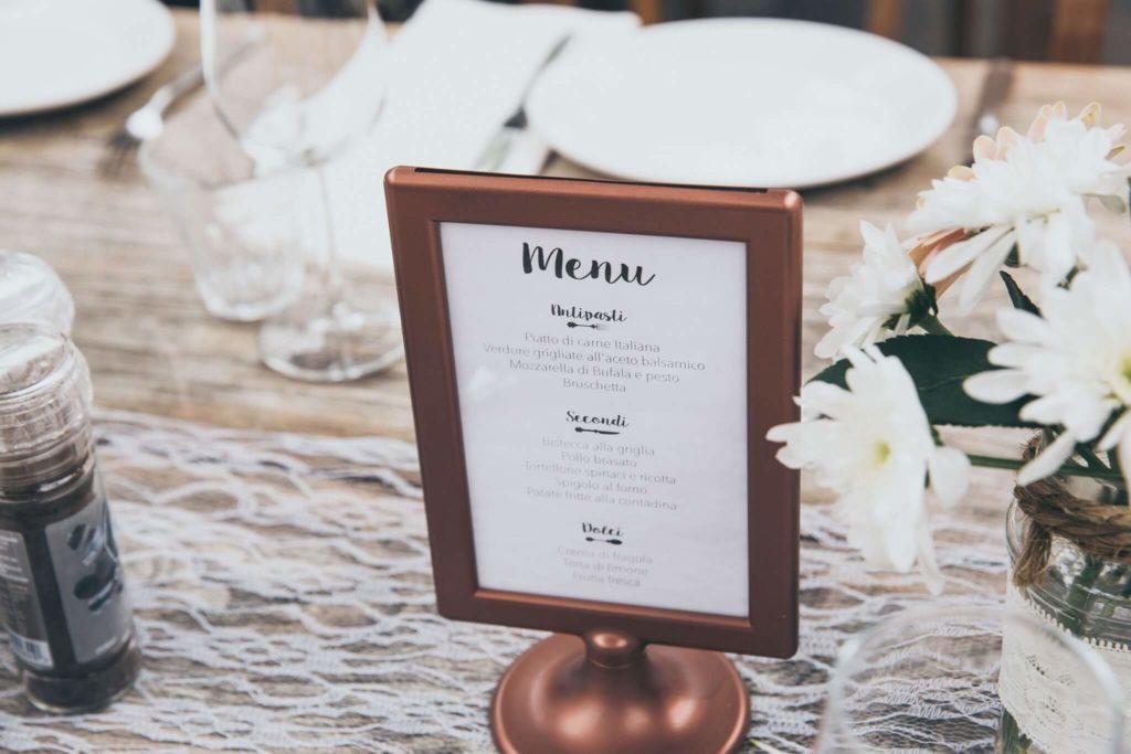 Menu affiché dans un petit cadre sur une table préparée pour un repas