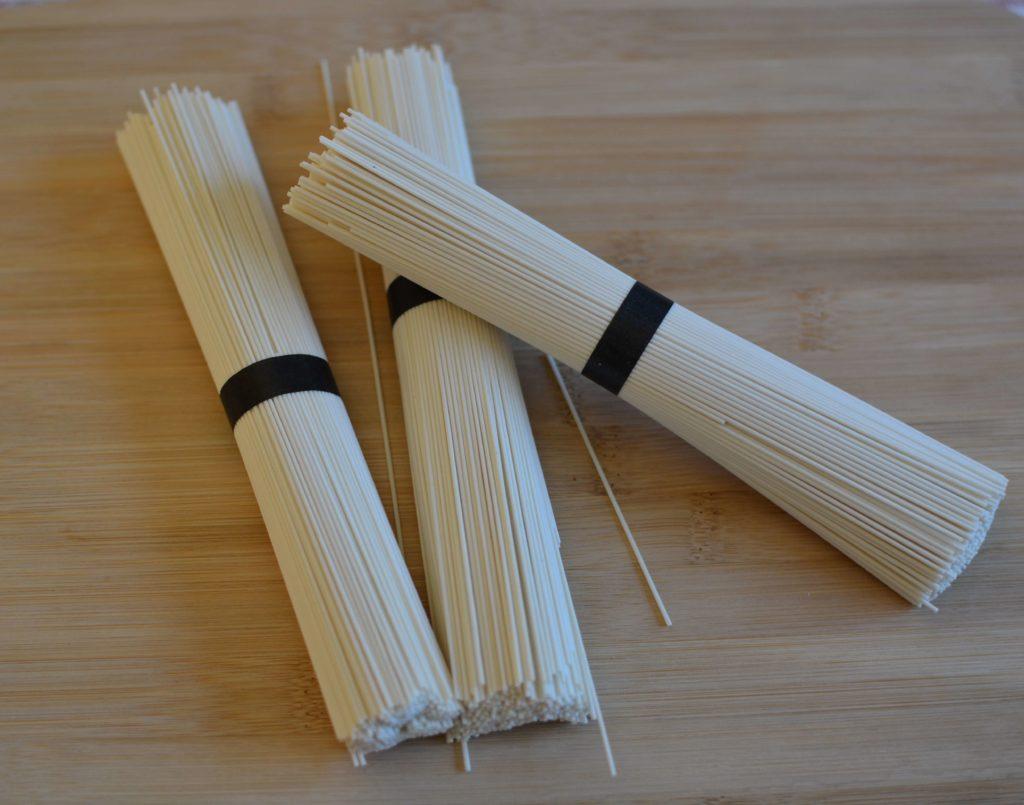 3 paquets de nouilles japonaises blanches sur une planche en bois