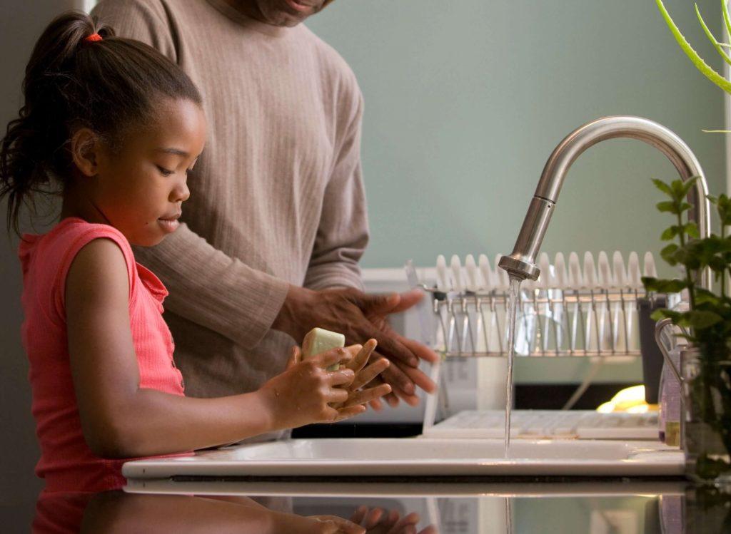 Petites fille en train de se laver les mains dans une cuisine
