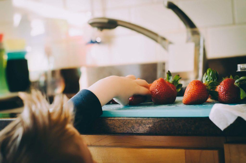 Main d'enfant attrapant une fraise sur un plan de travail