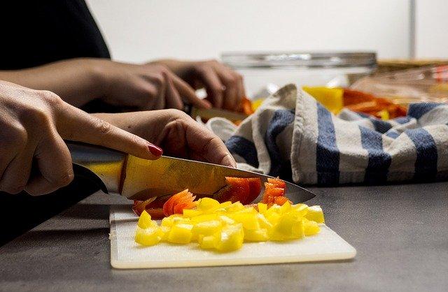 Main de femme en train de couper des poivrons