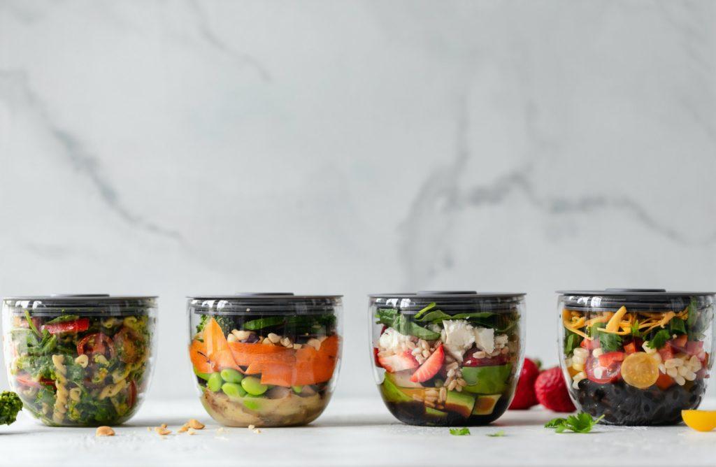 4 boites en plastique transparant contenant des salades composées
