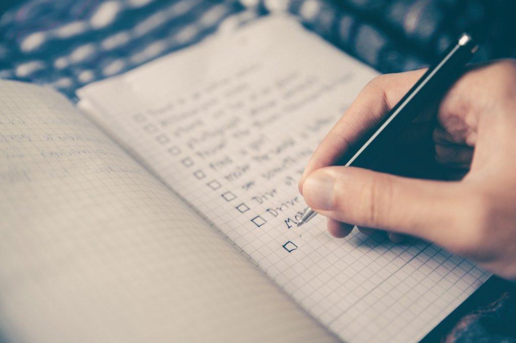 Main tenant un stylo en train d'écrire sur une cahier une liste