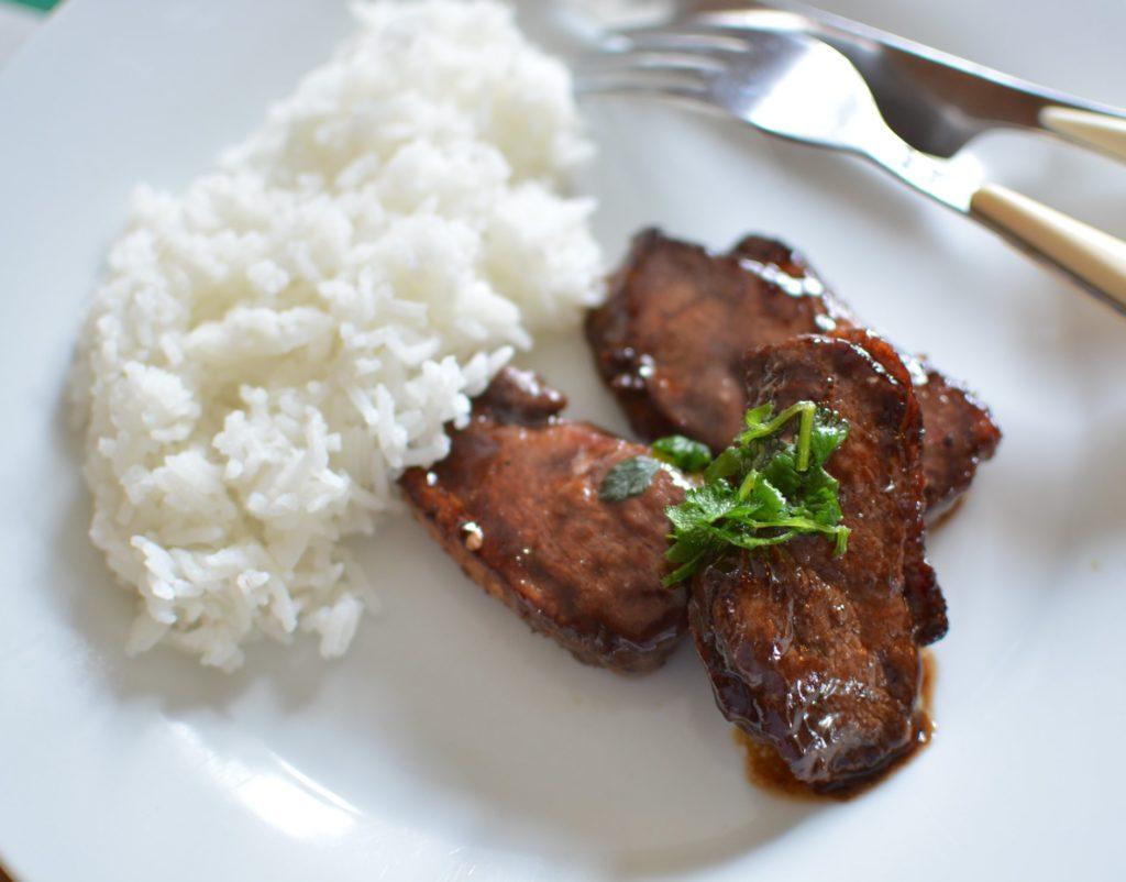 Tranche de viande dans une sauce brune avec du riz dans une assiette blanche