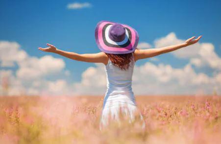 Femme debout de dos en robe blanche portant un chapeau dans un champ de blé,les bras écartés