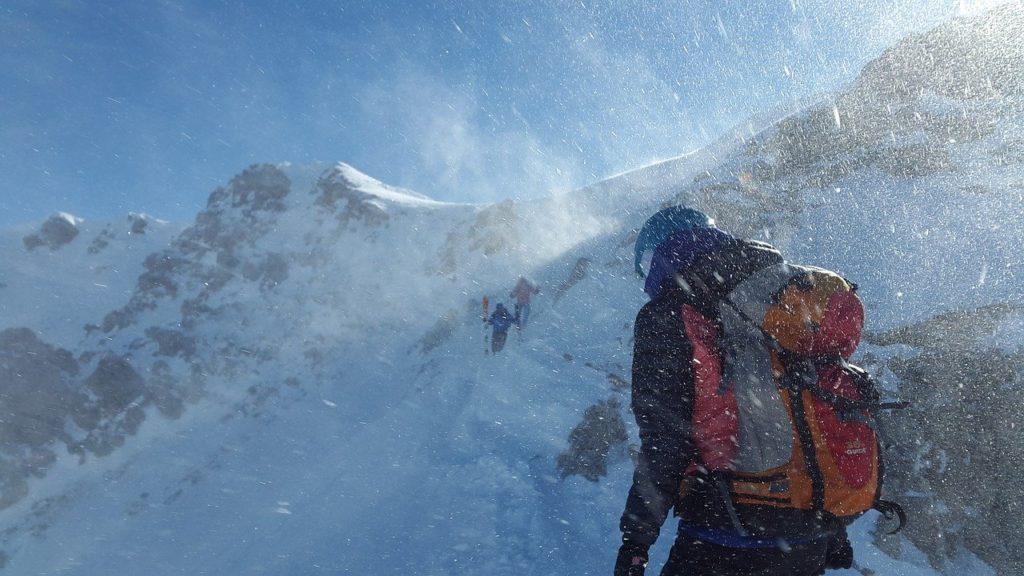 Personne de dos habillé avec un blouson et un sac à dos gravissant une montagne enneigée