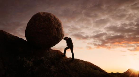 Homme sur une montagne poussant un rocher rond